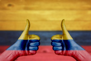 Colombia flag painted on female hands thumbs up with blurry wooden background